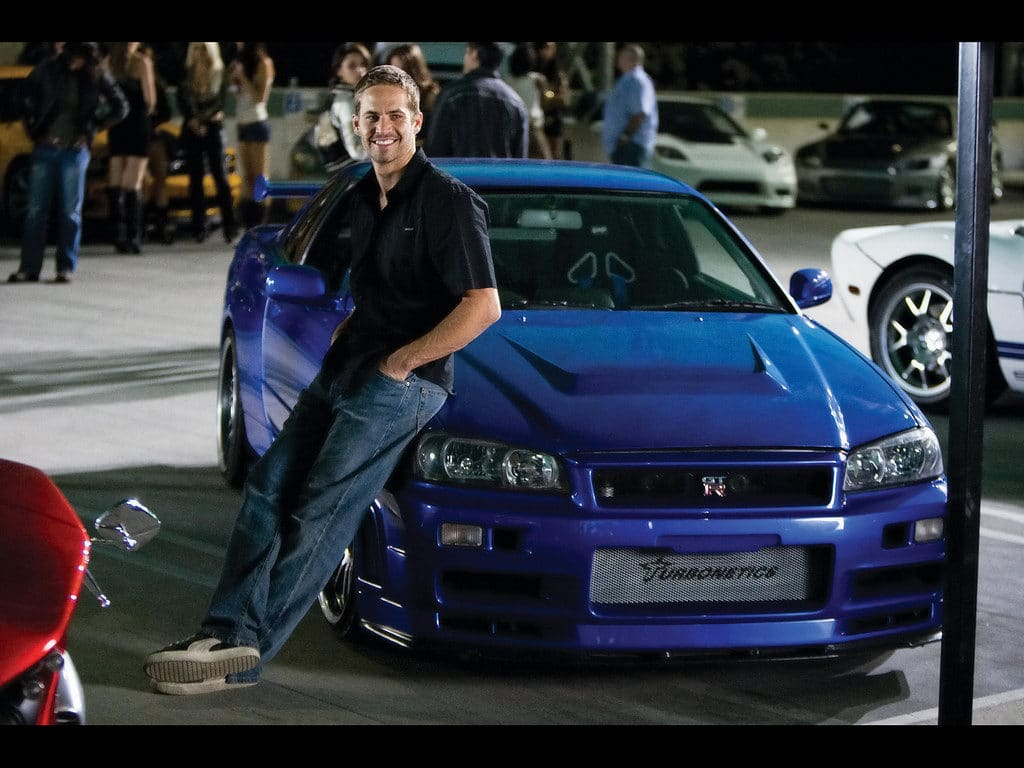 paul walker leaning against blue nissan skyline