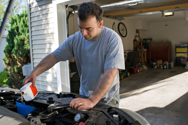 man changing car engine oil
