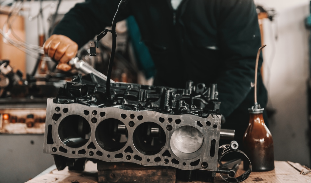 mechanic adjusting cylinder head on engine block